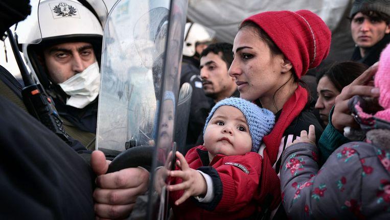 Vluchtelingen bij de afgesloten Grieks-Macedonische grens. Beeld afp