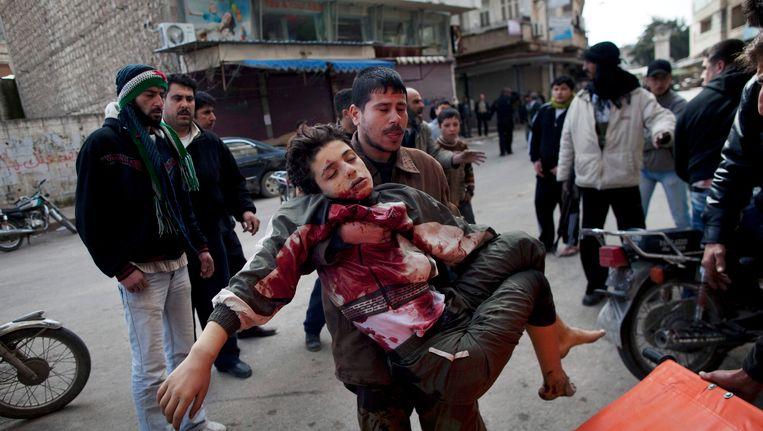 Een man brengt een jongen in veiligheid die werd geraakt door een sluipschutter in Idlib. Beeld AP