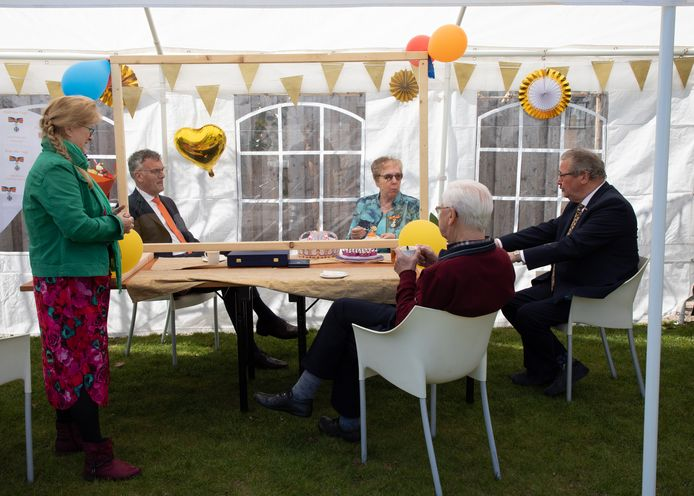 Burgemeester Janssen schuift voor het lintje voor Els Mommers-Van Tuyl aan in de partytent