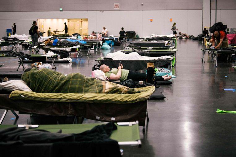 Mensen rusten uit bij een 'cooling station' in Portland, een plek waar ze kunnen ontsnappen aan de hitte. Beeld AFP