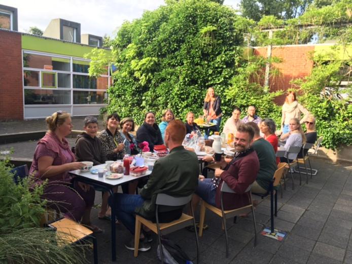 Leraren van basisschool De Carrousel in Gouda zitten in de tuin te ontbijten.