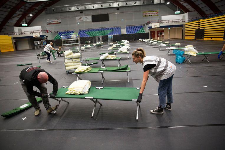 Vrijwilligers en Ready2Helpers toveren de Sporthallen Zuid om tot een daklozenopvanglocatie voor 75 personen ten tijde van het coronavirus.  Beeld Arie Kievit
