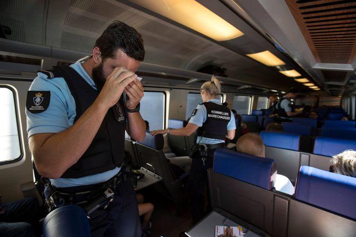 Marechaussees controleren identiteitsdocumenten in een trein.