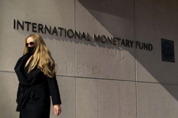 Een vrouw loopt langs het hoofdkwartier van het IMF in Washington. Archiefbeeld.