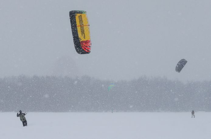 Deze enthousiastelingen maken van de wind gebruik om te gaan sneeuwkiten.