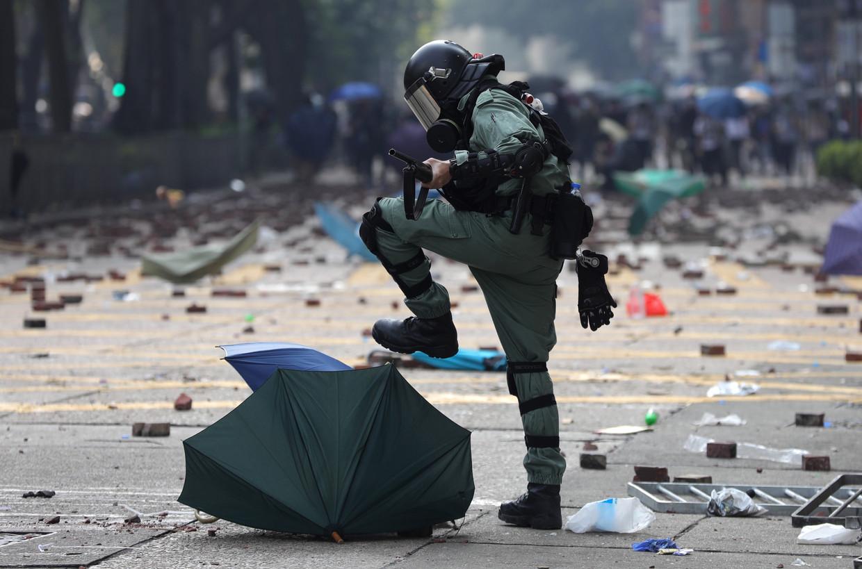 Een agent van de oproerpolitie stampt de paraplu van een demonstrant plat.