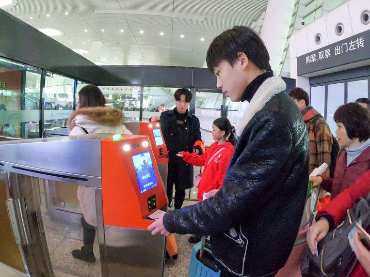 Een Chinees checkt door middel van gezichtsherkenning en een identiteitskaart in op een station in Hangzhou.  Beeld Visual China Group via Getty Images