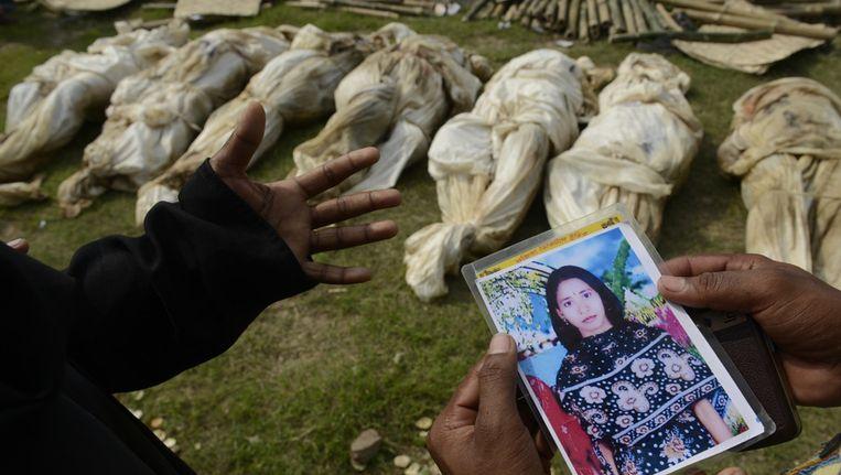 Een vrouw heeft de foto van haar zus bij zich, in de hoop haar te kunnen vinden tussen de lichamen die nog niet geïdentificeerd zijn. Meer dan 400 mensen zijn omgekomen toen een gebouw Dhaka, Bangladesh, instortte, waar onder slechte omstandigheden kleding werd gemaakt voor westerse merken. Beeld ap