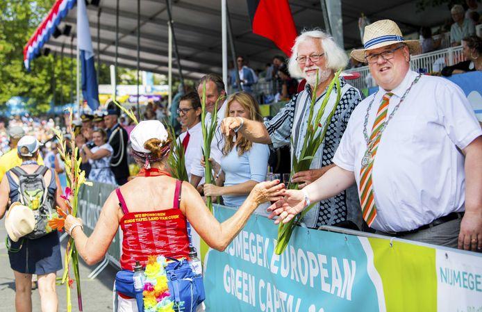 Nijmegens burgemeester Hubert Bruls (met hoed) tijdens de finish van de Vierdaagse-mars op de Via Gladiola. Nadat het wandelevenement voor komende zomer eerder al geschrapt werd, is er nu ook een streep gezet door de bijbehorende feesten.
