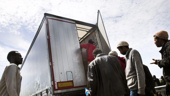 Migranten proberen aan boord te klimmen van een vrachtwagen