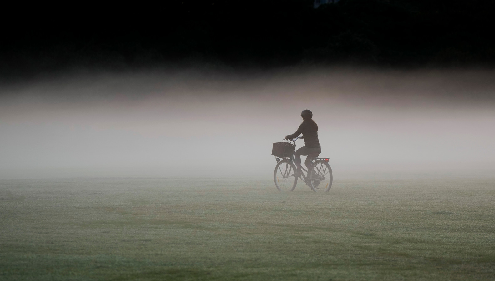A woman rides her bicycle through a heavy mist in a park as the sun rises in Sydney, Australia, Tuesday, May 25, 2021. (AP Photo/Mark Baker)