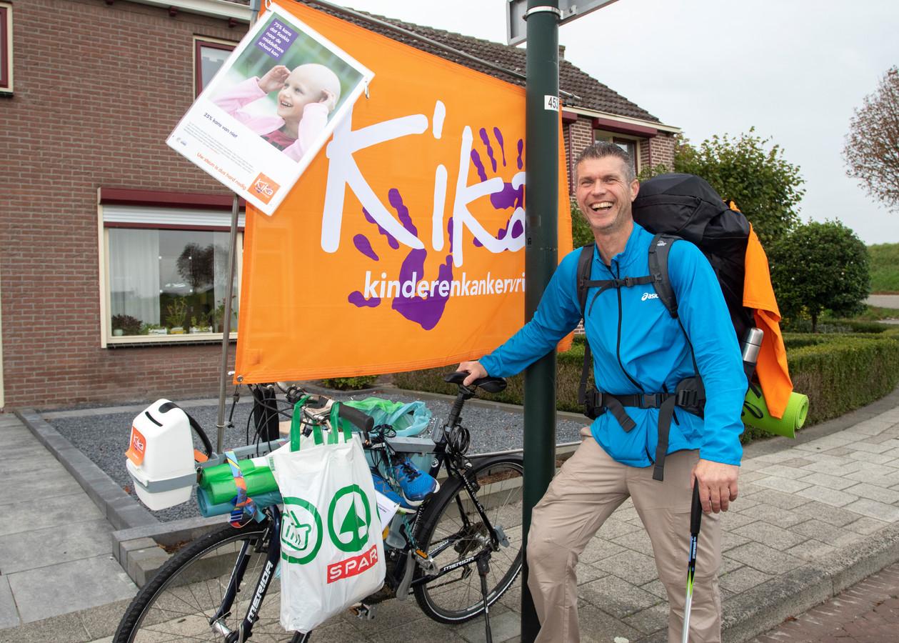Jaco van Halum bij z'n eerste tussenstop in Oud-Vossemeer. Hij loopt met de fiets in z'n hand. De collectebus zit voorop.