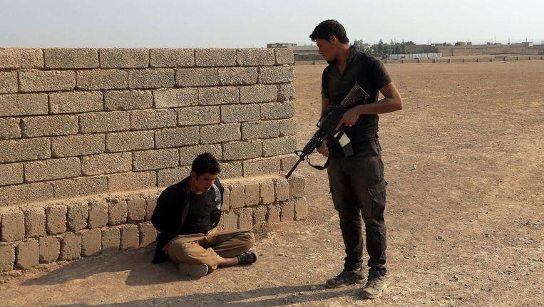Een lid van de Irakese contraterroristische troepen arresteert een man die verdacht wordt lid te zijn van IS. Beeld AP