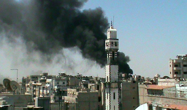 Een rookpluim steeg gisteren op uit een woonwijk in Homs. Beeld afp