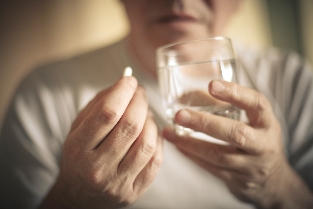 Senior man with pill. Focus is on hand. Close up. Beeld Getty Images