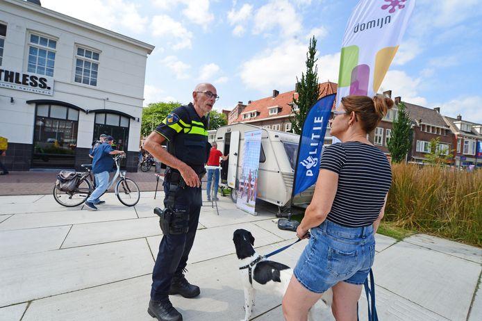Een buurtbewoonster laat politieman Marco van Zanten weten dat ze blij is met het nieuwe mobiele meldpunt tegen overlast.