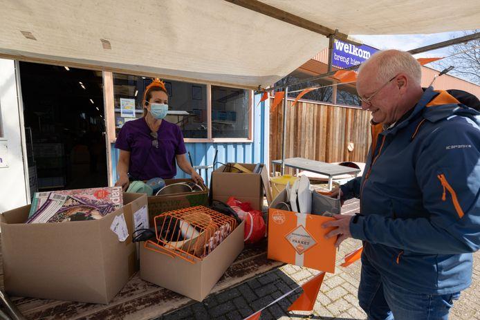 Huib van der Wal verblijdt Lara Jansen van Het Goed met dozen vol spulletjes voor de vrijmarkt op Koningsdag.