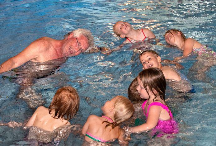 Leren zwemmen is een serieuze aangelegenheid, maar ook veel plezier maken, bewijst badmeester Erik met de kinderen van de Dorpsschool in Halle in het zwembad in Zelhem.