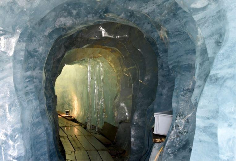 Het ijs in de grot komt van vallende sneeuw uit de tijd toen Bach en Beethoven nog leefden. Vandaag gutst en lekt overal smeltwater. 'Je hebt een paraplu nodig!' Beeld