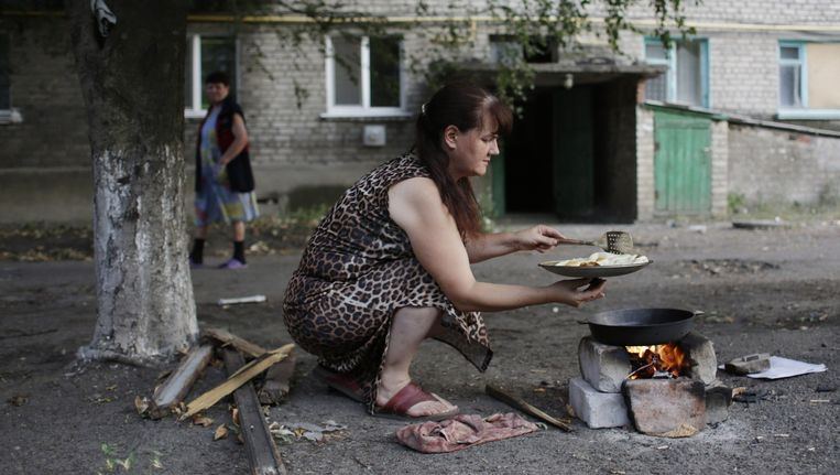 Een Oekraïense vrouw kookt op een kampvuurtje. Beeld anp