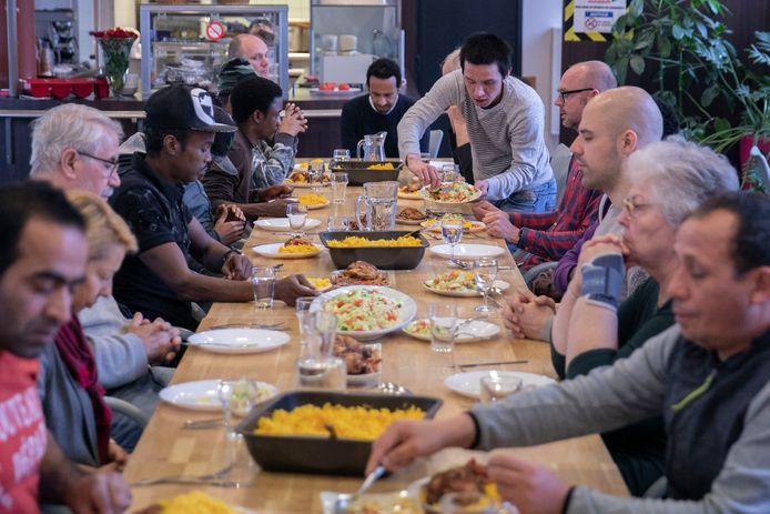 Vluchtelingen aan tafel in De Huiskamer in Eindhoven.