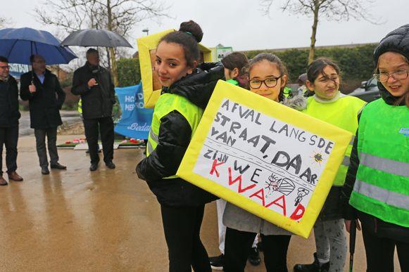 De leerlingen van de gemeenteschool kwamen het vernieuwde afvalstraatje mee inhuldigen en hadden ook enkele slogans bij.