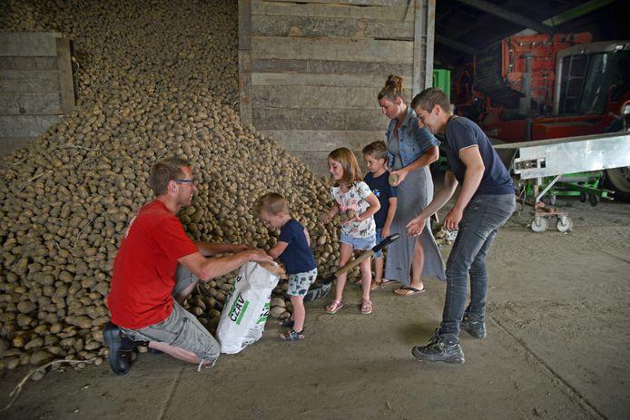 Geert van de Velde van Hoeve de Hond (rechts) met Adrie en Manon Tanis, hun kinderen Guus en Elize en Sem bij de aardappelberg in Dreischor
