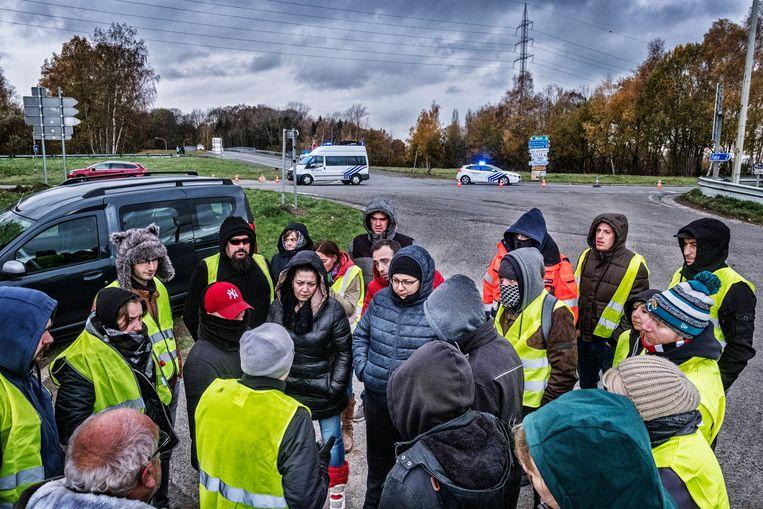 Een dertigtal 'gele hesjes' blijven op post in de buurt van het brandstofdepot in het Waalse Feluy, ook al heeft de politie de blokkade opgeheven.   Beeld Tim Dirven
