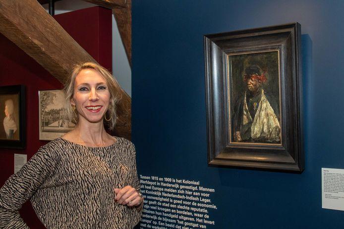 Conservator Sophie van Steenderen bij het portret van Kees Pop.