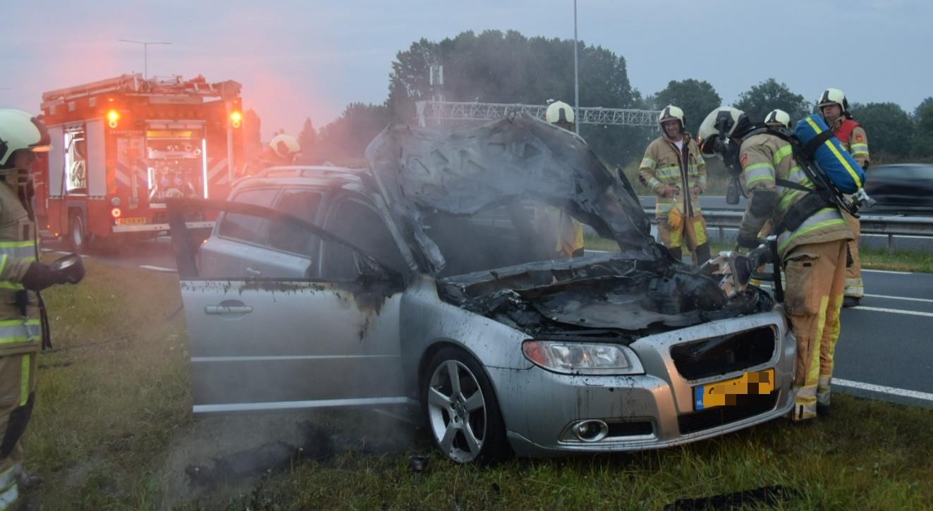 De brandweer blust de rokende auto.