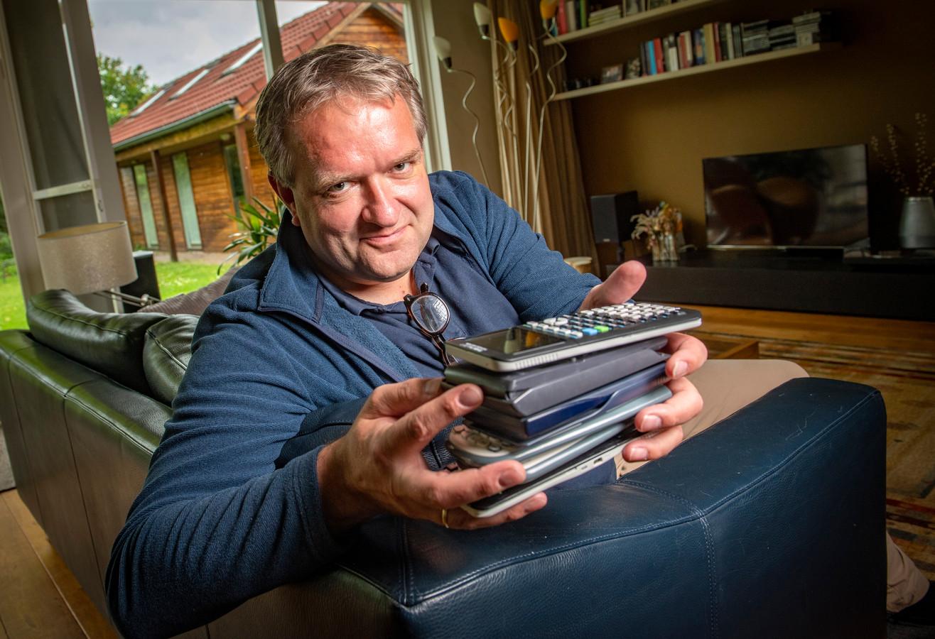 Vader Arjen van Gijssel met een stapel rekenmachines in zijn hand. De stapel wordt met het jaar groter. Zijn jongste dochter (14) heeft sinds dit schooljaar ook weer een nieuwe nodig.