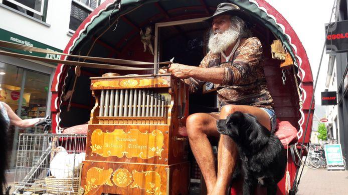Ruud draait in het centrum van Winterswijk aan het orgeltje op de bok van zijn kleine huifkar.