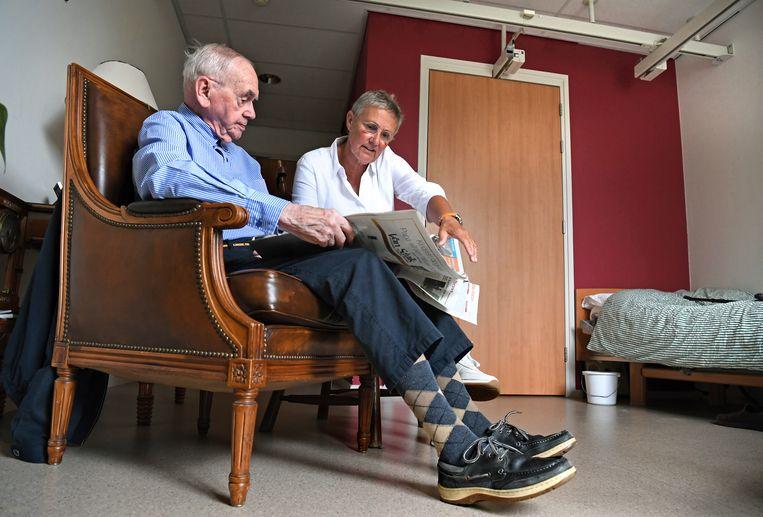 Heleen Gerwig helpt haar vader in verpleeghuis de Tabakshof in Elst bij het lezen van de krant.   Beeld Marcel van den Bergh / de Volkskrant