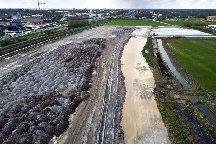 Een foto van het terrein uit april 2021. De grijs-zwarte hopen links zijn een mengsel van staalslakken en menggranulaat (gebroken puin).
