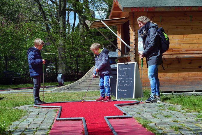 Sem, Bas en moeder Eefje tikken een balletje op de minigolfbaan in Bergen op Zoom.