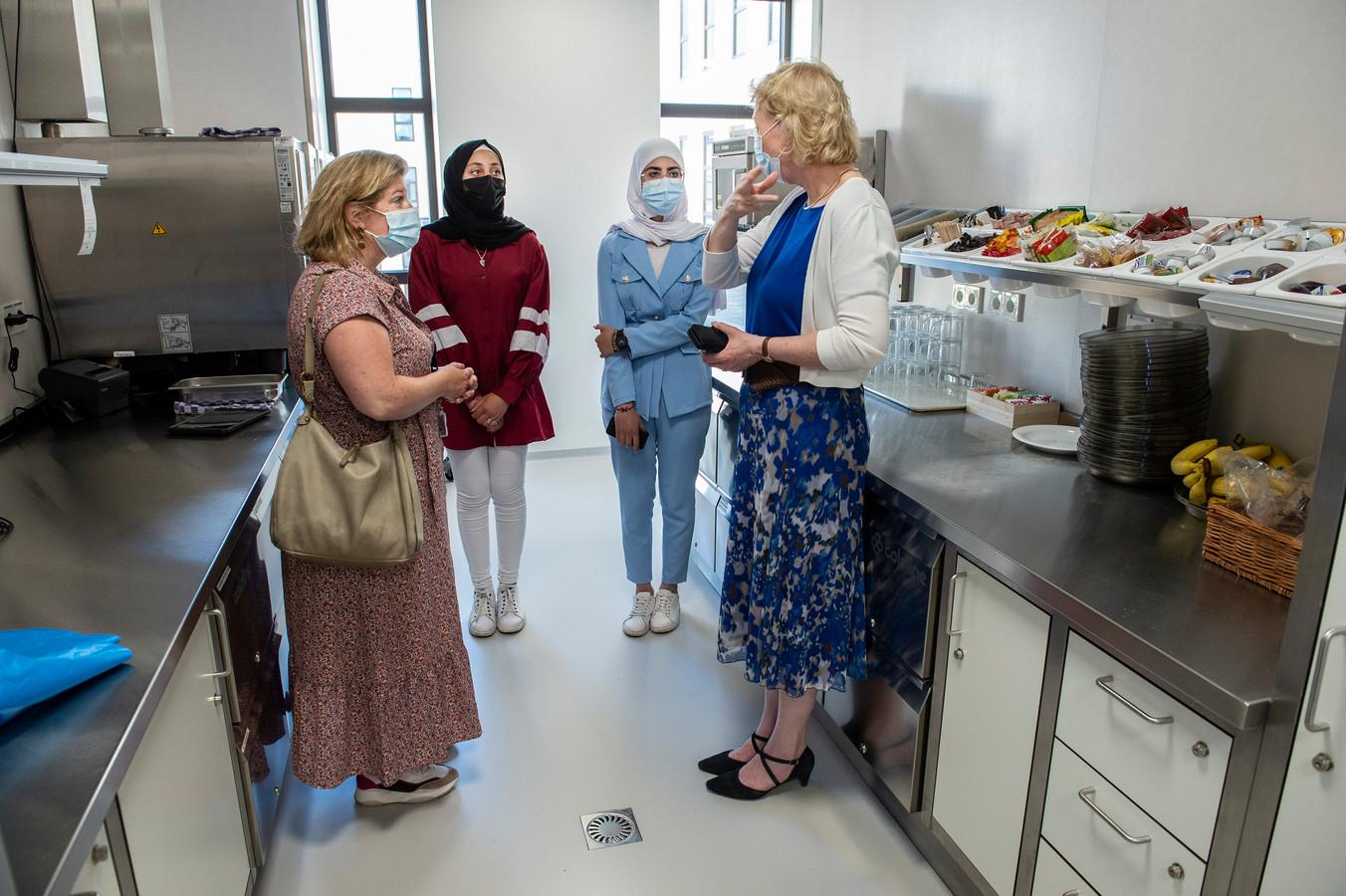 Aya (tweede van links) en Malika (tweede van rechts) krijgen uitleg in een keukenruimte van het Amphia ziekenhuis.