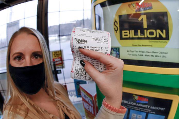Une vendeuse montre le billet de Mega Millions.