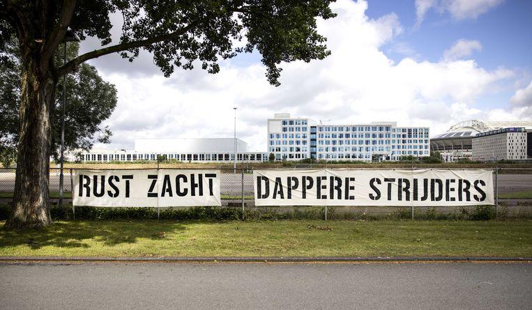 Op de parkeerplaats net naast de Toekomst is een spandoek opgehangen met de tekst 'Rust Zacht. Dappere Strijders'. Beeld ANP