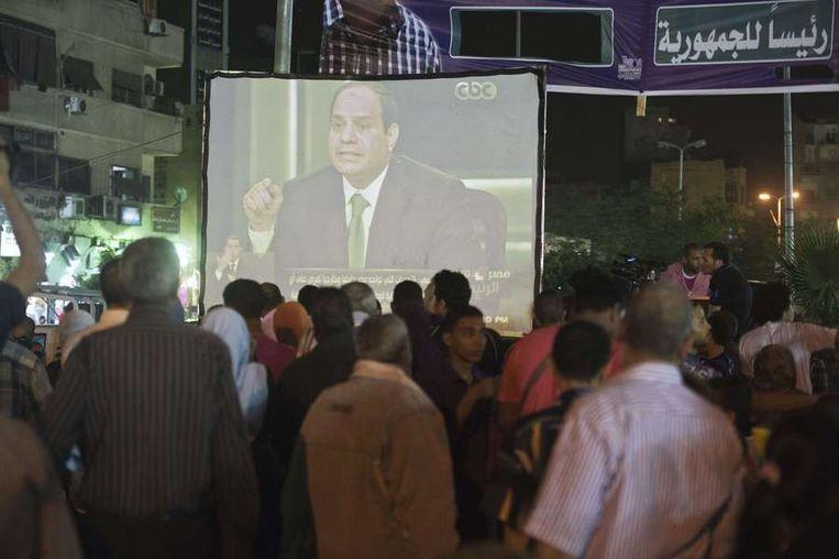 Op straat in Caïro wordt het interview met Sisi op een groot scherm uitgezonden Beeld afp