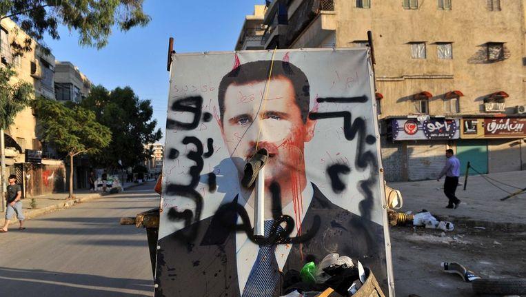 Een poster van president Assad ligt bij het oud vuil in de Syrische stad Aleppo. Beeld afp