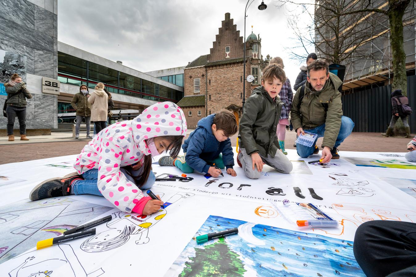 Kinderen in de weer voor vluchtelingen bij het stadhuis in Arnhem. Daar werd zondag de actie Lopend Vuur gehouden, waarin aandacht voor de leefomstandigheden van vluchtelingen wordt gevraagd.