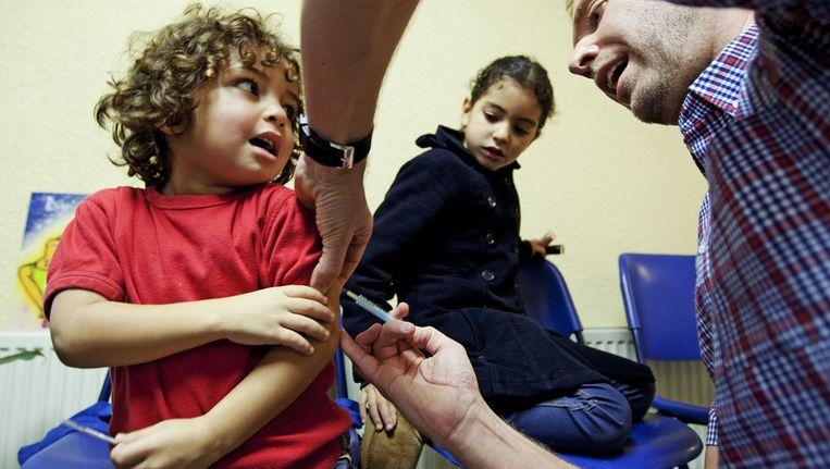 Een huisarts in Amsterdam dient een vaccin tegen Mexicaanse griep toe. Beeld ANP