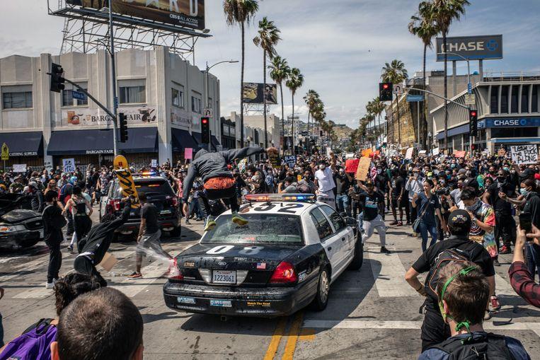 Een politiewagen moet eraan geloven. Straatprotesten, zoals hier in Los Angeles, naar aanleiding van de dood van George Floyd kaartten de rassenongelijkheid in Amerika aan – een thema dat Biden nauw aan het hart ligt. Beeld NYT