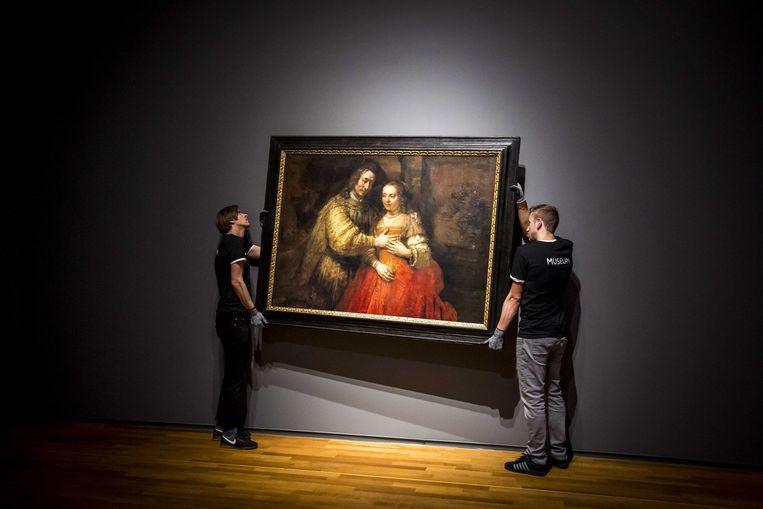 Het schilderij 'Het Joodse bruidje' van Rembrandt van Rijn wordt opgehangen in het Amsterdamse Rijksmuseum, vier dagen voor de publieksopening van de tentoonstelling 'Alle Rembrandts'. Beeld ANP