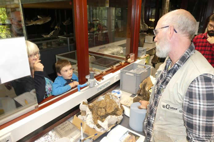 Aart Walen in het laboratorium bij het Oertijdmuseum in Boxtel in gesprek met een jonge bezoeker over de botten van de Diplodocus.