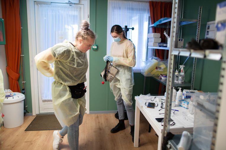In een kamer in de 'oranje zone' trekken studenten verpleegkunde van het Graafschap College hun beschermende kleding uit voor een pauze. Beeld Herman Engbers