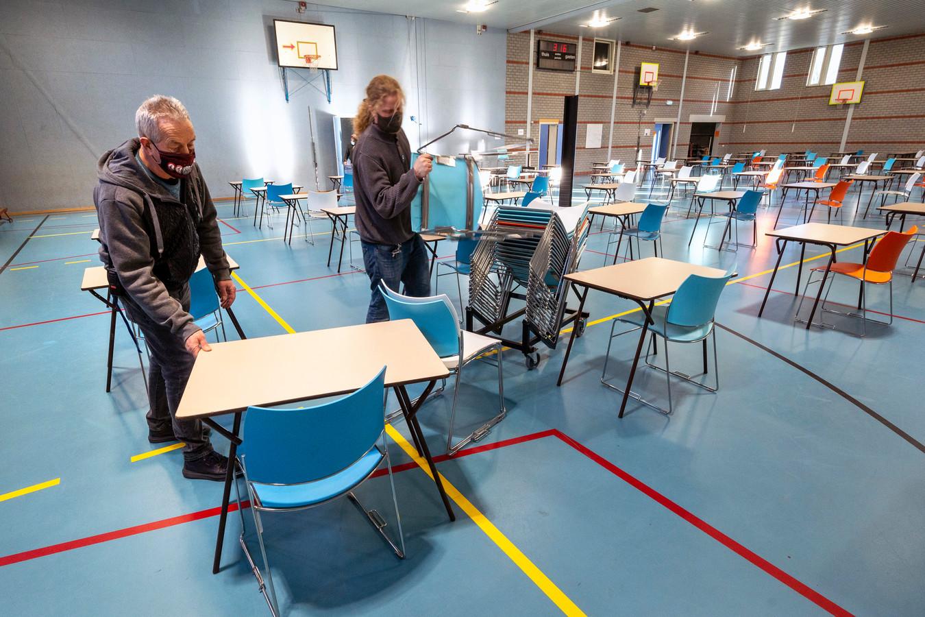 Bij het Olympus College worden in de gymzaal in allerijl tafels en stoelen met anderhalve meter afstand van elkaar gezet voor het maken van toetsen door eindexamenklassen.
