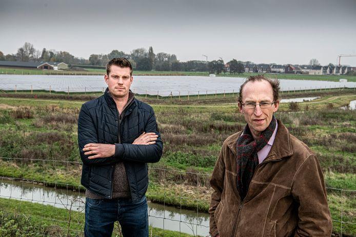 Voorzitter van Vitaal Druten Geert van Bergen (l) met voorzitter Jan van Lent van ZLTO Maas en Waal met op de achtergrond een van de twee zonnevelden in Beneden-Leeuwen.