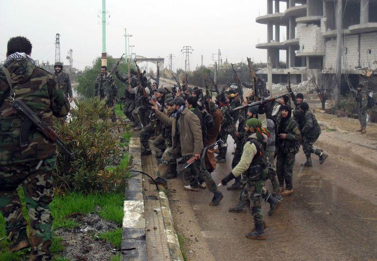 Syrische strijders aan de kant van Assad vieren het heroveren van het dorp Sheikh Miskeen in de zuiderlijke Daraa provincie op 26 januari, 2016. Beeld afp