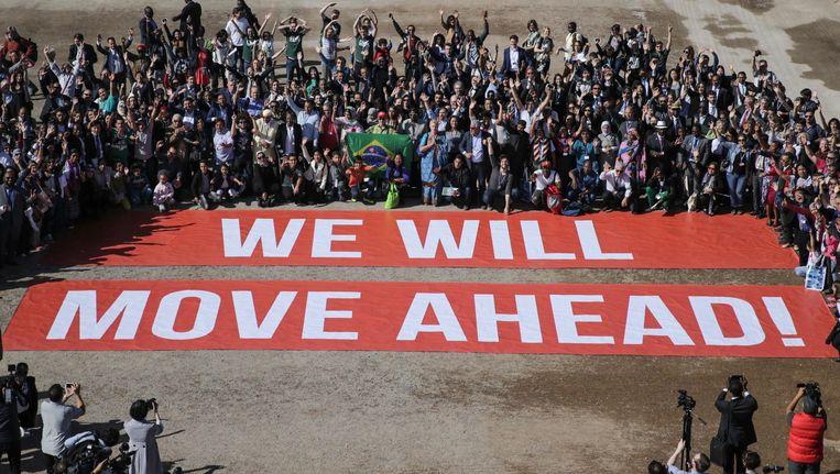 Deelnemers aan de VN-conferentie over Klimaatverandering in het Marokkaanse Marrakesh scharen zich rond een groot spandoek met 'Wij zullen vooruitgang boeken'. Beeld AP